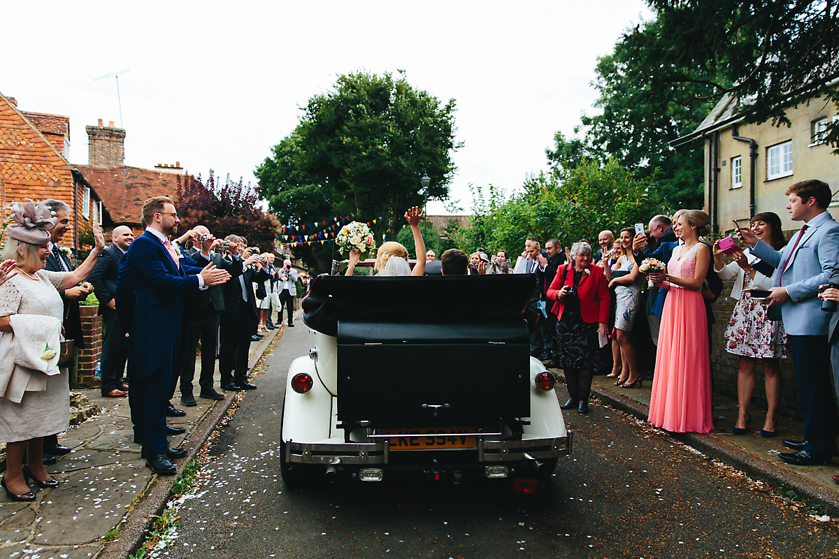 Bride and groom leaving in their vintage wedding car