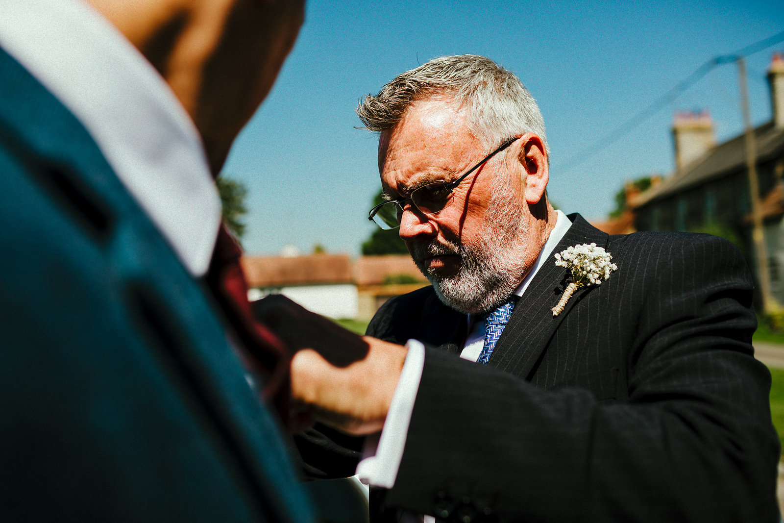 Father of the groom helping with buttonhole