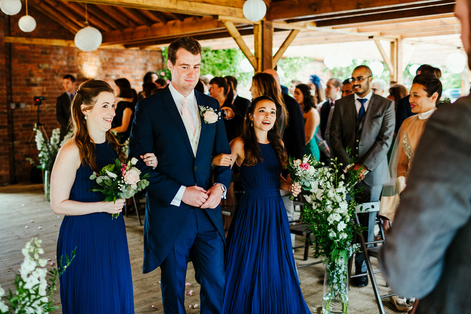 Bridesmaids walking down the aisle at Orchardleigh walled garden