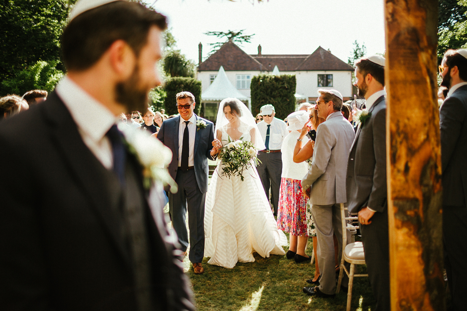 Father of the bride walking down the aisle in summer wedding