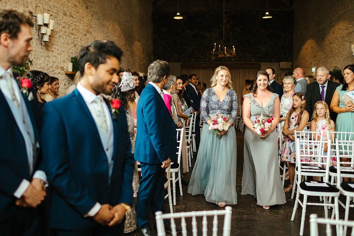Bridesmaids walking down the aisle in grey dresses