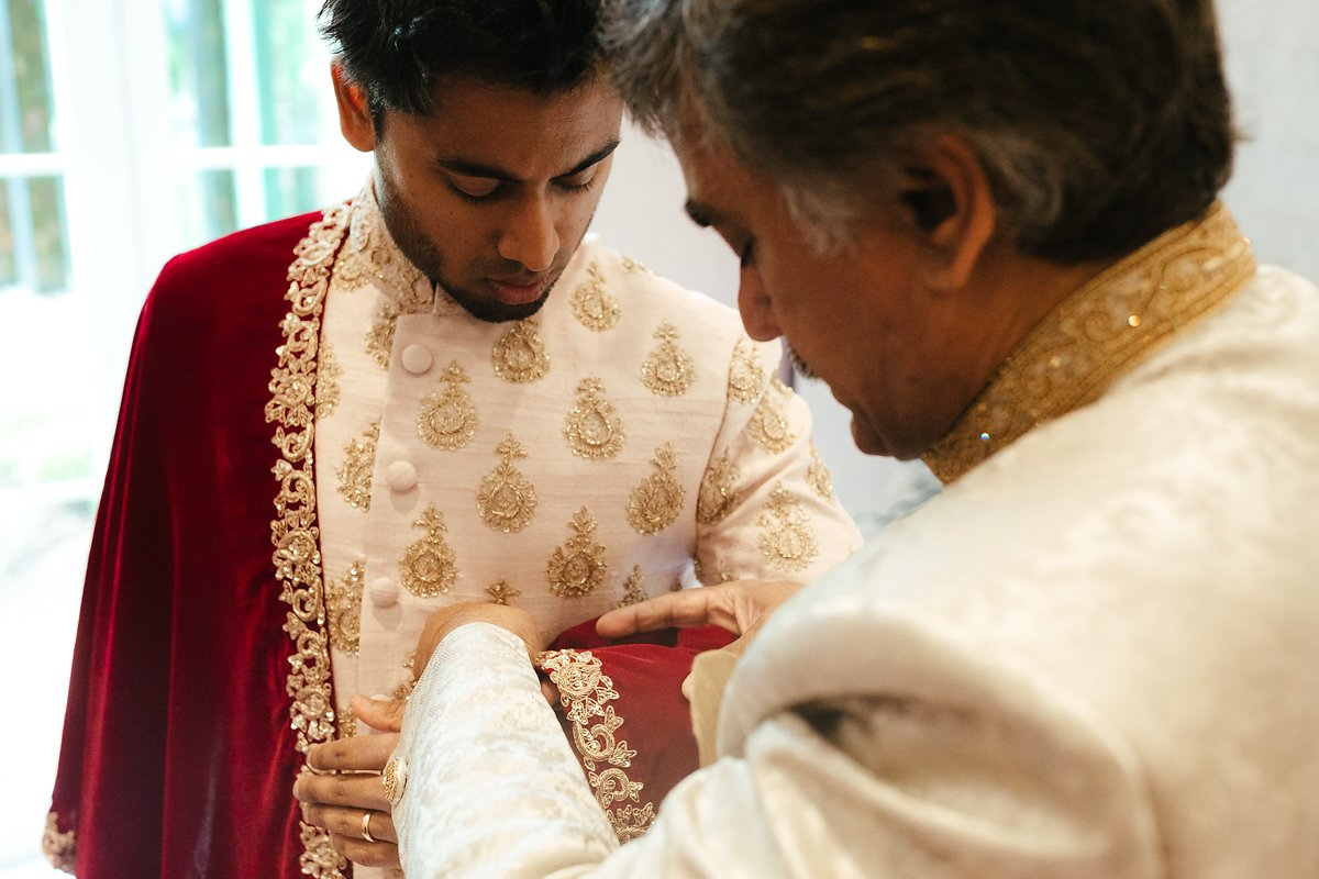 Dad and uncle helping the groom to get ready at Indian wedding