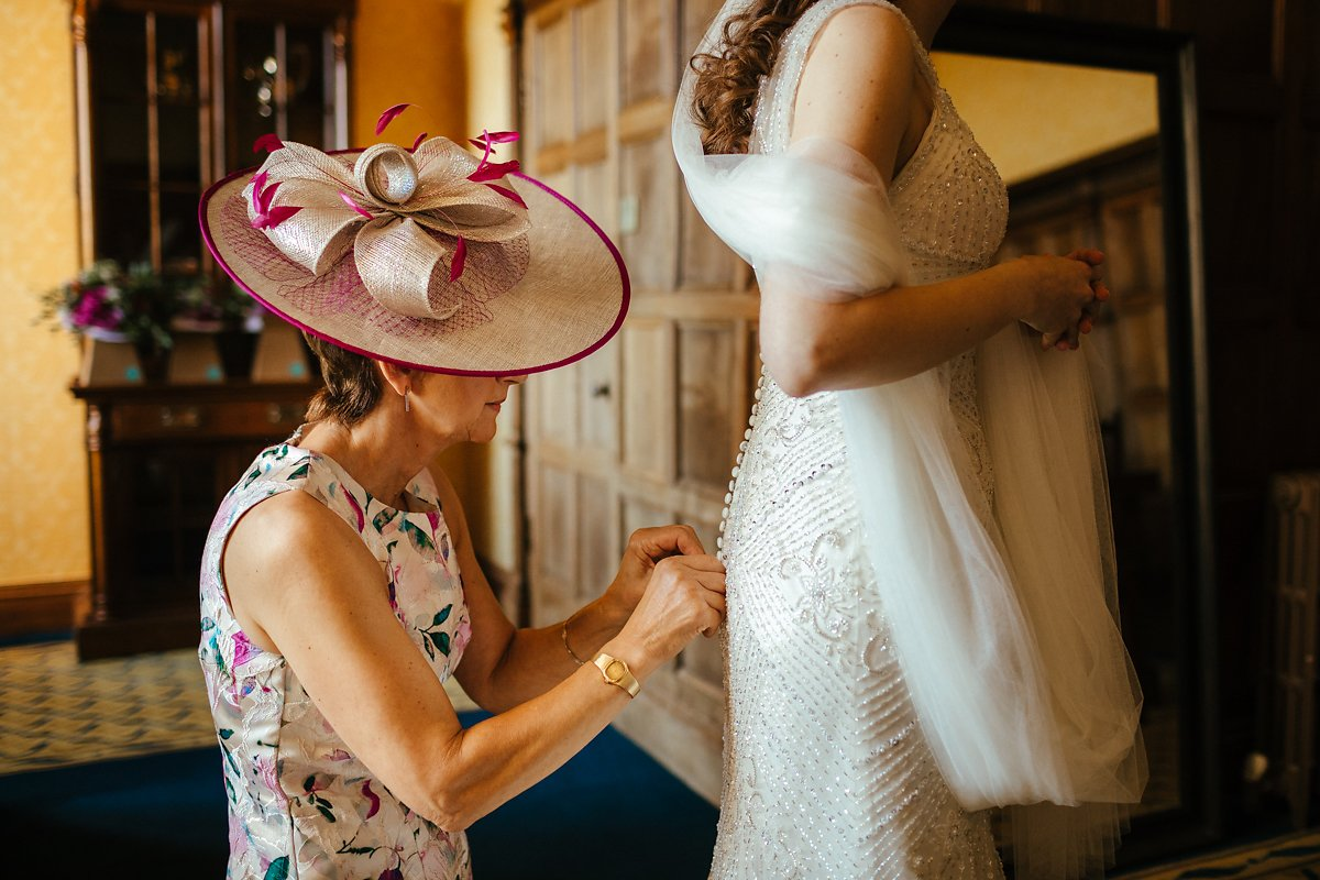 Mum helping bride to get dressed